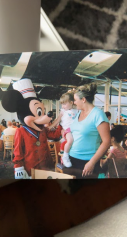Senior Emily McNulty standing next to Mickey Mouse in her mom's arms in 2005.                                                      Photo Courtesy: Emily McNulty.